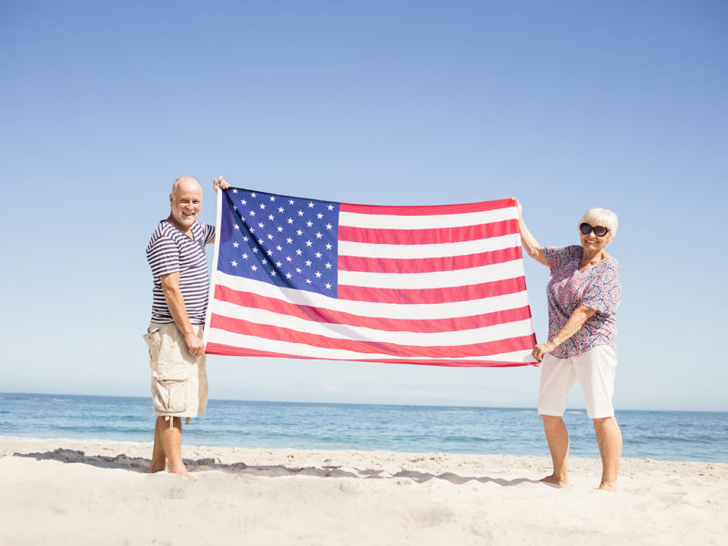 two seniors holding an American flag on the beach.