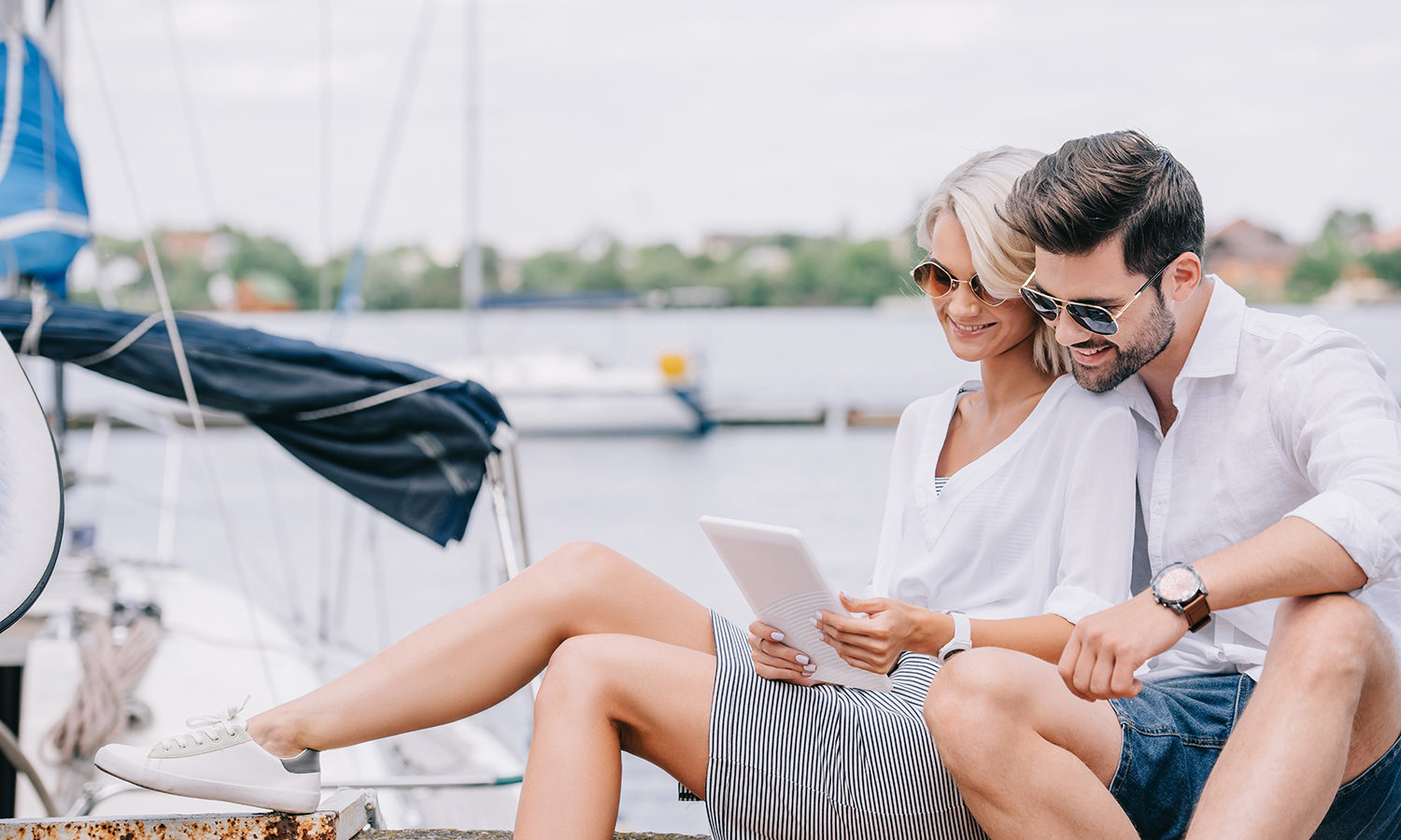 couple in a marina looking at a tablet