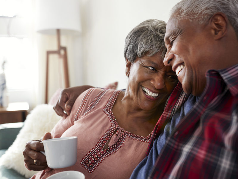 an older couple laughing over coffee